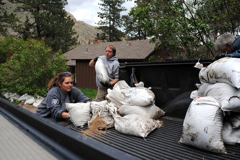 Americorps volunteers Ashley Sandmann, left, and Shawn Decker, right, load torn sandbags into a truck on Monday May 20, 2013.