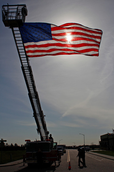 "The morning sun shines through an American flag hung over Clydesdale Parkway Sunday morning in Loveland. Veterans participating in ""Honor Flight Northern Colorado"" headed to Denver International Airport by bus and passed under the flag. They will be flying to Washington, D.C., to visit war monuments."