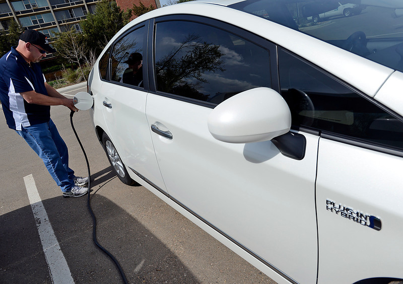 Michael Koenig of Loveland plugs his Toyota Prius Plug In Hybrid car to a public charging station at a parking lot on First Street and Monroe Avenue in downtown Loveland on Monday, May 13, 2013.
