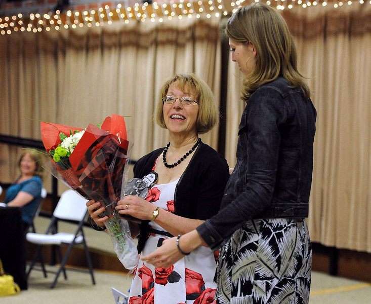 Dixie Schmatz, left, is presented with flowers by her daughter, Katie Schmatz, moments after being honored as the Rotarian of the Year by the Loveland Rotary Club at The Garden Room in Loveland on Tuesday, May 14, 2013.