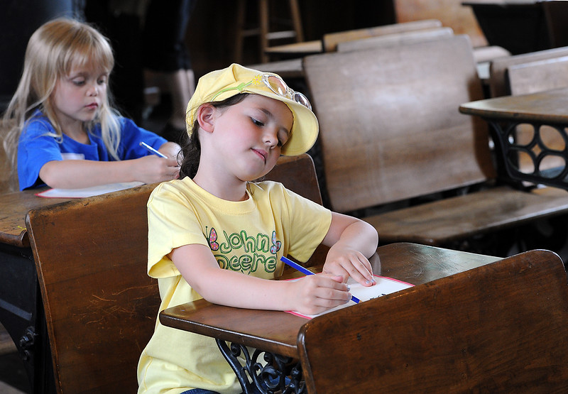 Bailey Gibson, front, and Abby Simpkins, back, draw pictures while sitting at desks inside the Lone Tree School  at North Lake Park during an ice cream social held by the Loveland Museum/Gallery in Loveland on Wednesday, May 15, 2013.