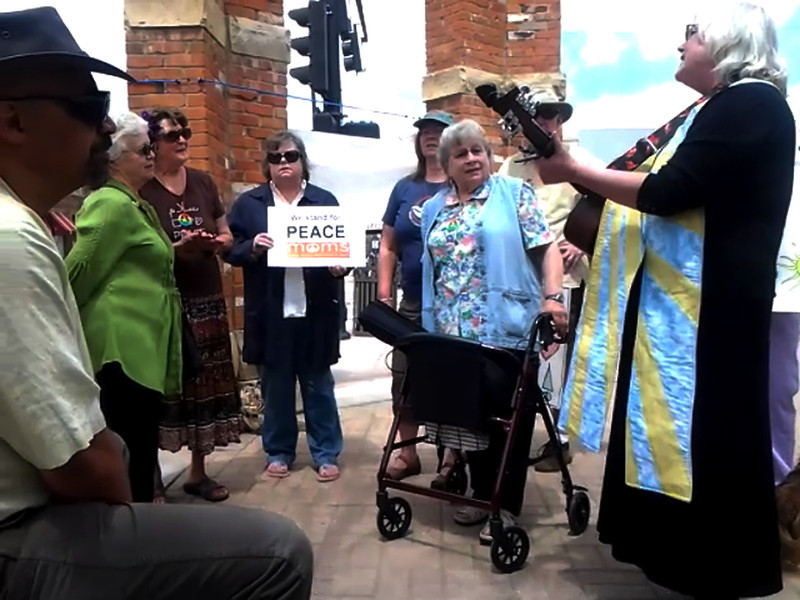 Minister for the Namaqua Unitarian Universalist Congregation, Laurel Liefert, right, leads members and friends of the congregation in singing songs about peace Sunday afternoon while participating in the Mother's Day Stand for Peace at Thompson Park in Loveland.