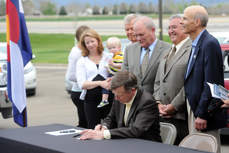 Colorado Gov. John Hickenlooper, middle, signs an alternative energy vehicle bill during a signing ceremony on Wednesday, May 15, 2013 at the City of Loveland's Water and Power Division.