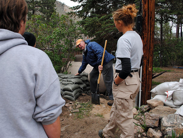 Poudre Park homeowner, Bob Smith, center, shows Americorps volunteers how to place sandbags around his neighbor's property on Monday May 20, 2013.