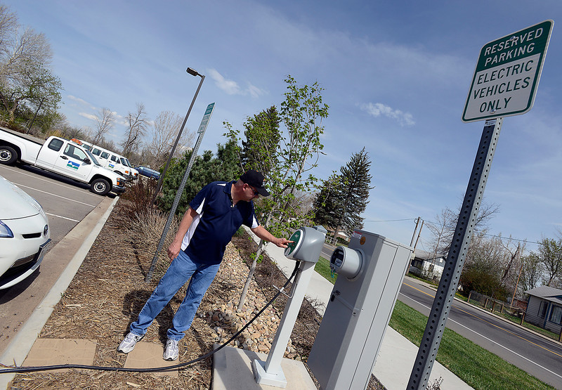 After plugging his Toyota Plug In Hybrid car into a public charging station, Michael Hoenig presses a button on the station to start the charging process in a parking lot on First Street and Monroe Avenue in Loveland on Monday, May 13, 2013.