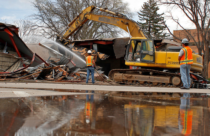 Brinkman Partners crews demolish the old Home State Bank building Tuesday afternoon at Sixth Street and Lincoln Avenue in Loveland. The building is being cleared and will soon have a five-story apartment complex built on the site.
