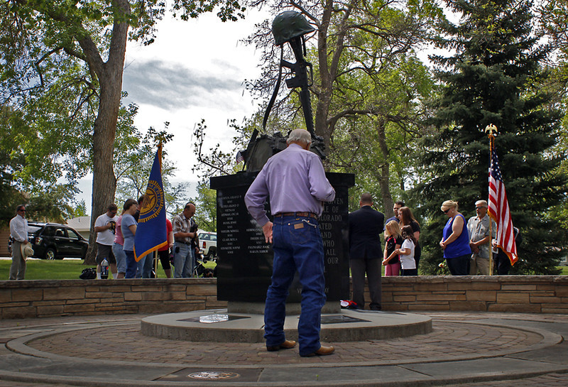 Observers at a Memorial Day ceremony put on by Loveland's own American Legion Post 2000 at Dwayne Webster Veterans Park, pray together to honor fallen U.S. veterans, Monday morning in Loveland. (Photo by Timothy Hurst)