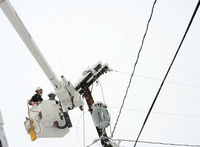 City of Loveland power employees Tobin Roitsch, left, and Eric Duhn work to replace a lightning arrester on a power pole on the 3000 block of Waterdale Drive in west Loveland on Wednesday, May 1, 2013. Moisture from the snow may have broken the part, causing a power outage to a few homes in the area.