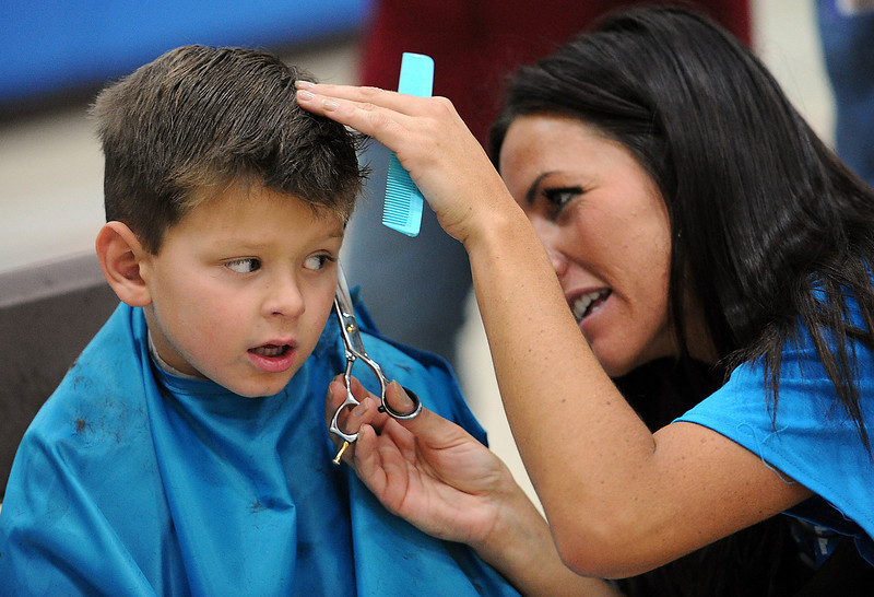 Hayden Benton, 4, tries to hold still as volunteer Amelia Parker, with Hair Dynamics Education Center, cuts his hair during the first annual Loveland Homeless Connect event at Truscott Elementary School. Hayden lives with his great-grandmother at the Angel House.