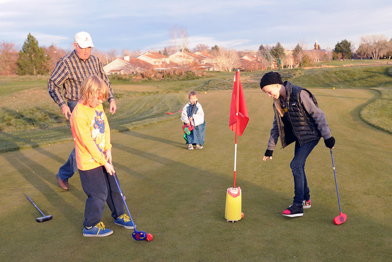Loveland resident Larry Combs, back left, and his grandchildren, Aidan Rowley, 10, Kingston Clous, 6, and Sydney Rowley play a round of SNAG golf on Friday, Nov. 23, 2012 at Cattail Creek Golf Course. The Rowley's are visiting from San Carlos, Calif. and Kingston is from Fort Collins.
