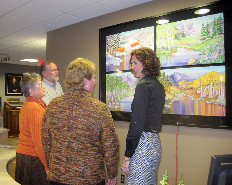 Artist Jean Batchelder, left, talks to Marilyn Schock, CEO of McKee, and Marcie Erion, Creative Sector Development, about the four-painting series she designed for the McKee Medical Center main lobby. Batchelder's husband, Jamie Bethel, admires the painting in the background. The watercolor artwork was unveiled Tuesday.