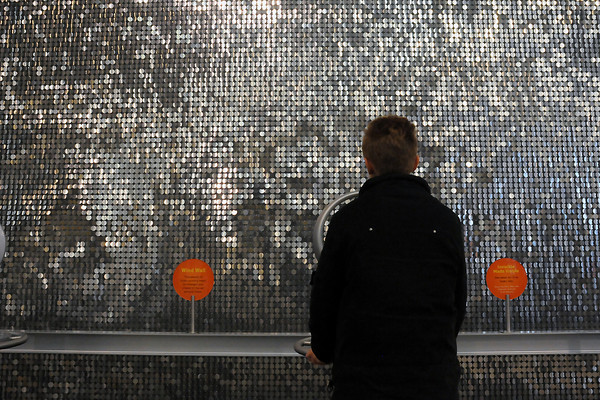 A boy blows air at a wall of loose-hanging discs that shimmer in the breeze to show the movement of air at the Fort Collins Museum of Discovery on Saturday. (Photo by Craig Young)