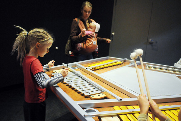 Laila Buehl, 6, of Loveland makes music in the xylophone room at the Fort Collins Museum of Discovery on Saturday as her mother, Missy, tries her hand while toting 10-month-old Indie.
