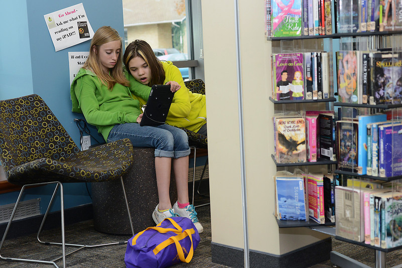 Bill Reed Middle School sixth-graders Danielle Taylor, 12, left, and Maya Bontrager, 11, use an iPad tablet computer last Wednesday, Nov. 1, 2012 in the teenseen section of the Loveland Public Library.