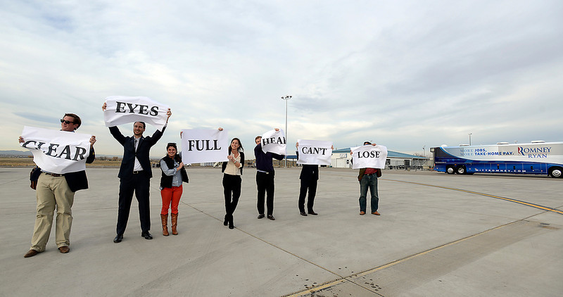 Members of the Romney/Ryan Colorado campaign staff hold up signs for Paul Ryan to see as his plane takes off from the airport in Loveland Monday after speaking in Johnstown.