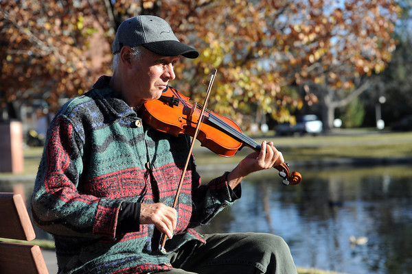 """Loveland resident Steve Roslund sits on a park bench alongside Foote Lagoon while playing his fiddle Tuesday, Nov. 2012. Roslund said he's been playing the fiddle off-and-on for about forty years and added, """"It's just a nice day to be outside."""""""