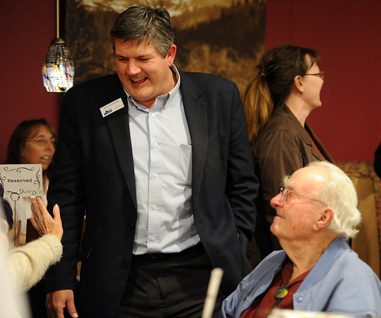 Larimer County Commissioner Tom Donnelly talks with supporters including Warren Wolaver, right, a long time former Larimer County Commissioner, Tuesday at the LaQuinta Inn in Loveland.