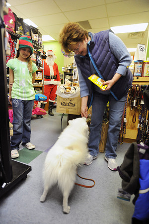 Haleigh Deubach, 9, left, and Kyle Anderson, dressed as Santa Paws, look on while Rackel Ward feeds a treat to her dog named Mr. Big during the Holiday Pix with Santa Paws event on Saturday, Nov. 24, 2012 at Hank's Pet Food Market, 2245 W. Eisenhower Blvd.