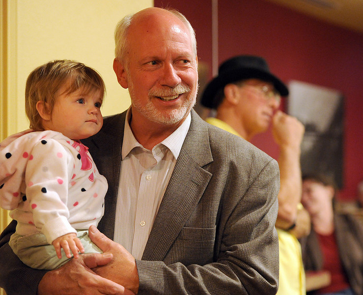 Dave Clark watches results come in as he holds his granddaughter Avea Clark, 1, Tuesday evening at the LaQuinta Inn in Loveland.