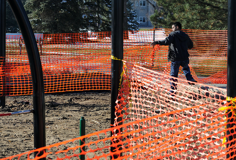 Richie Donnelly, with Tatonka, secures a construction fence around the playground equipment after he and a crew installed new rubber surfacing in the play area at North Lake Park in Loveland.