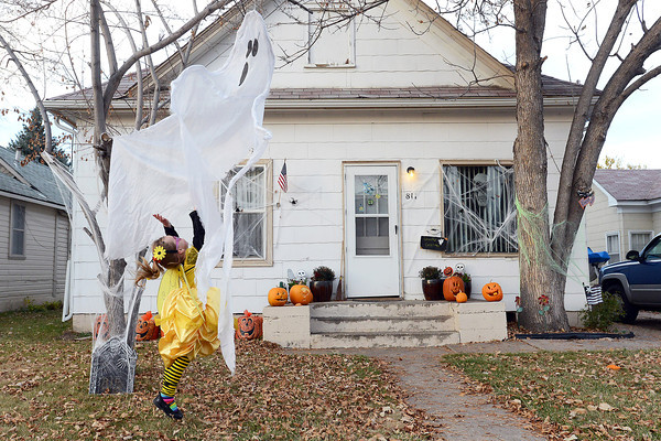 Three-year-old Madeline Tungl is dressed as a bumblebee princess as she leaps in the air while scampering around the Halloween decorations in the front yard of her home in downtown Loveland on Wednesday, Oct. 31, 2012.