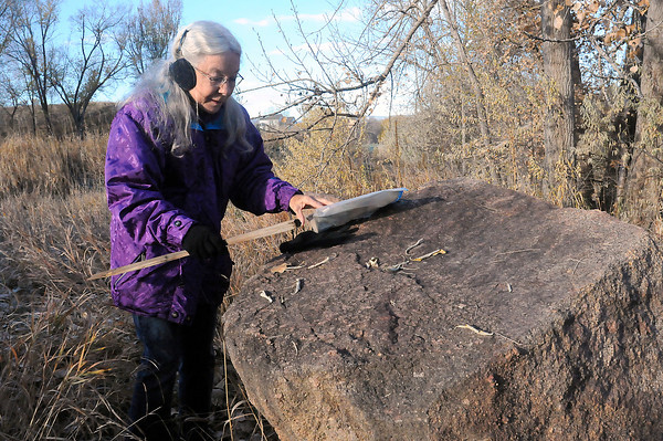 """Loveland Historical Society member Sharon Danhauer removes a """"this rock is reserved"""" sign that she'd placed two years ago next to a boulder off the 15th tee at Mariana Butte Golf Course. The rock was moved Friday morning, Nov. 9, 2012, to a spot at the Mariano Medina family cemetery, where it will hold a plaque describing the role of the Cherokee and Overland trails. The route of the historic 19th century trails runs through the area."""
