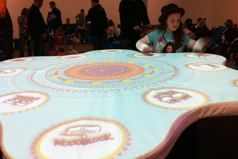 Zoe Johnson, 7, of Fort Collins gets some whacks in on the big drum table at the Fort Collins Museum of Discovery on Saturday. (Photo by Craig Young)