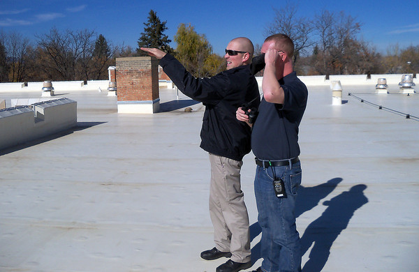 Network systems engineers Josh Coseo, left, and Derrick Hoffman identify a weather balloon from the roof of Bill Reed Middle School that they are using to help measure heights for network systems equipment at Thompson School District.