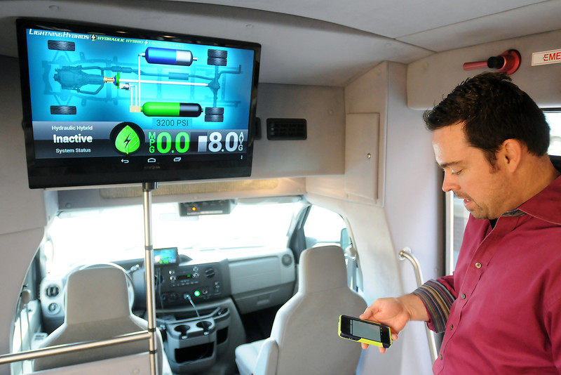 Tim Reeser, president of Lightning Hybrids, uses his smartphone to access an information screen that tells riders how the Loveland company's hydraulic hybrid technology is working. When the system is installed in two city buses, passengers will be able to keep tabs on the big screen behind the driver or on their mobile devices. (Photo by Craig Young)