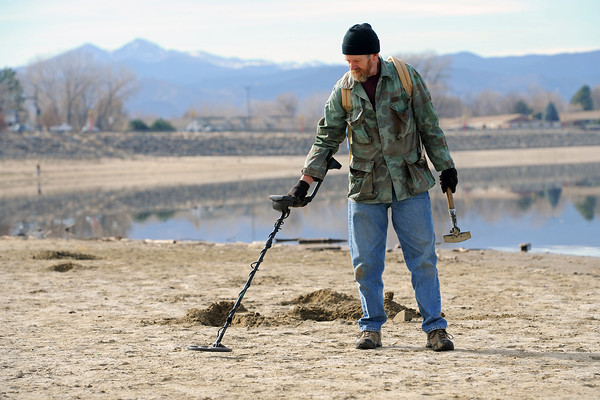Longmont resident Jim Stanoff uses his metal detector to search along the south shore of Lake Loveland on Saturday afternoon. Stanoff said he picked up the hobby about 15 years ago and was metal detecting at the lake with his son, David, who lives in Loveland.