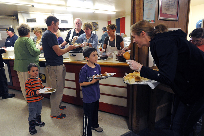 Volunteer Tori Kricken, right, serves a dinner roll to Caleb Morrow, 7, during a free Thanksgiving meal event on Thursday, Nov. 22, 2012 at the Loveland Associate Veterans Club.