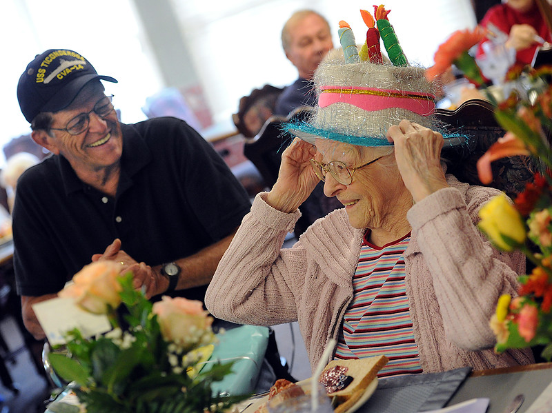Hertha Kuehl tries on her birthday hat as her son Jim Kuehl, left, smiles, Friday as she celebrates her 100th birthday with family and friends at The Courtyard of Loveland.