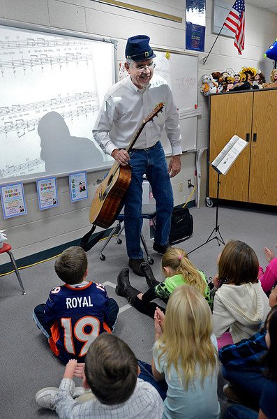 Volunteer Lou Price chats with second-graders after playing his guitar and leading them in song Tuesday at Namaqua Elementary School in Loveland. In honor of Read Aloud, Price read the students a book about Abraham Lincoln before they sang a song about him.
