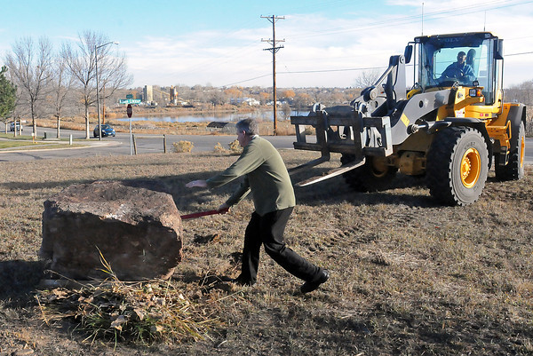 Steve Southard, golf operations manager for the city of Loveland, motions to the rock that Dick Ward had just deposited Friday morning with a front-end loader at the site of the Medina family cemetery. The rock, which had been stored with several others near the 15th tee at Mariana Butte Golf Course, will have a plaque affixed to it telling the history of the Cherokee and Overland trails. The property,  northwest of the corner of West First Street and Namaqua Avenue in west Loveland, recently was donated to the Loveland Historical Society, which will preserve the cemetery as a historical site. Loveland pioneer Mariano Medina's settlement and crossing over the Big Thompson River are farther west along Namaqua Avenue, across from Namaqua Park. Loveland Historical Society members Sharon Danhauer, Ann Ague and Pam Sheeler watched the rock's placement.