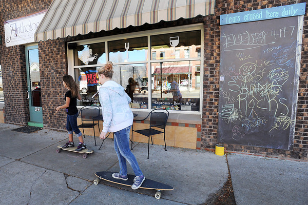 Maya Deeb, 13, left, and Breannah Duffey, 14, skate past one of the be lab's community chalk boards outside Anthology Book Co. in downtown Loveland on Tuesday, Nov. 20, 2012.