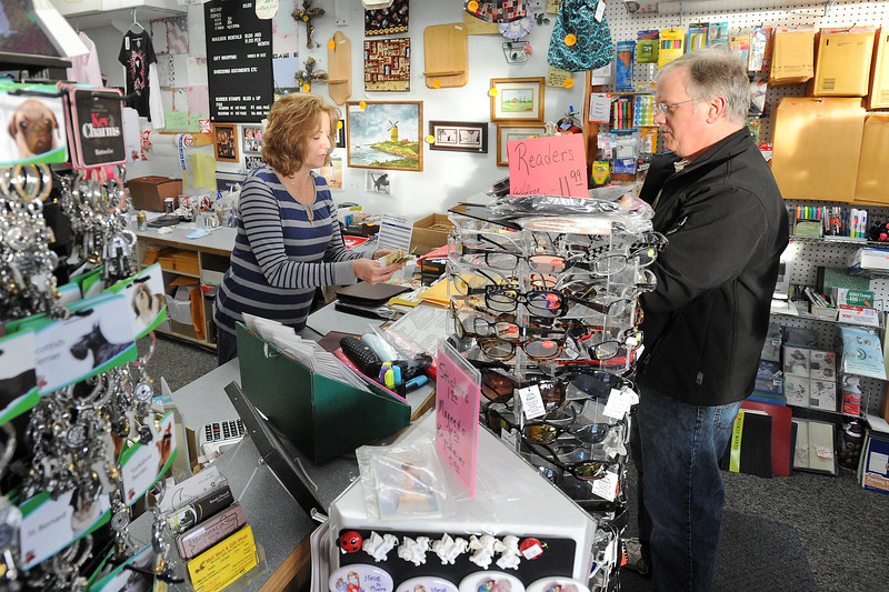 Mail Mart & Gift Shop owner Cyndi Scott, left, assists Steve Nelson with a transaction on Friday, Nov. 23, 2012. The store is located at 117 E. 37th St. in north Loveland and is participating in the Small Business Saturday promotion which encourages people to do their holiday shopping on Saturday at locally owned stores.