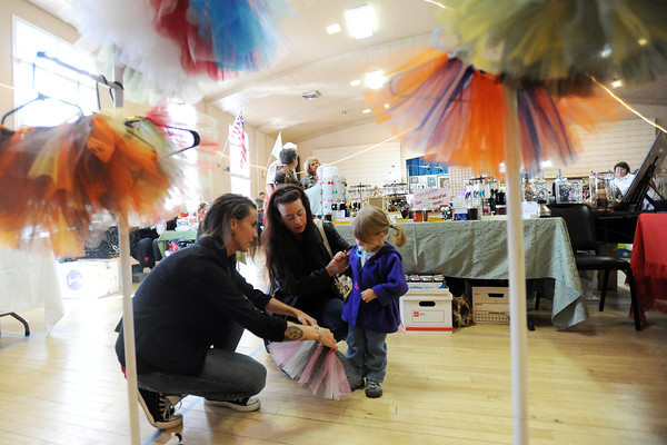 Amanda's Lil' Bloomers owner Amanda Richter, left, assists Melissa Shrader and Kaitie Shrader, as they look at tutus during the Loveland Elks Arts and Crafts Show on Saturday, Nov. 3, 2012 in downtown Loveland.