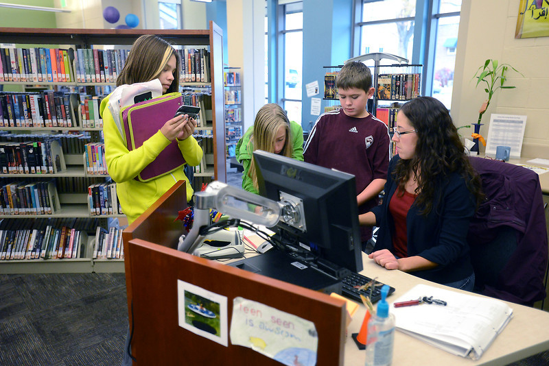 Teen librarian Michelle Turner, right, assists Maya Bontrager, 11, left, Danielle Taylor, 12, and Coleton Huggins, 12, last week in the teenseen section of the Loveland Public Library.