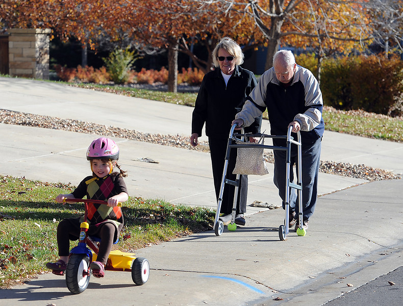 Elaine Bonnell, left, walks with her husband Elmer Bonnell as she keeps a close eye on her granddaughter Kate Ward, 3, riding her tricycle recently in their Loveland neighborhood.