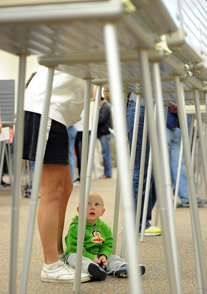 Sitting on the floor under a voting booth, Asher Ristau, 18 months, looks up at his daycare provider Nikki Basart as she votes Tuesday at the Loveland Police and Courts building.