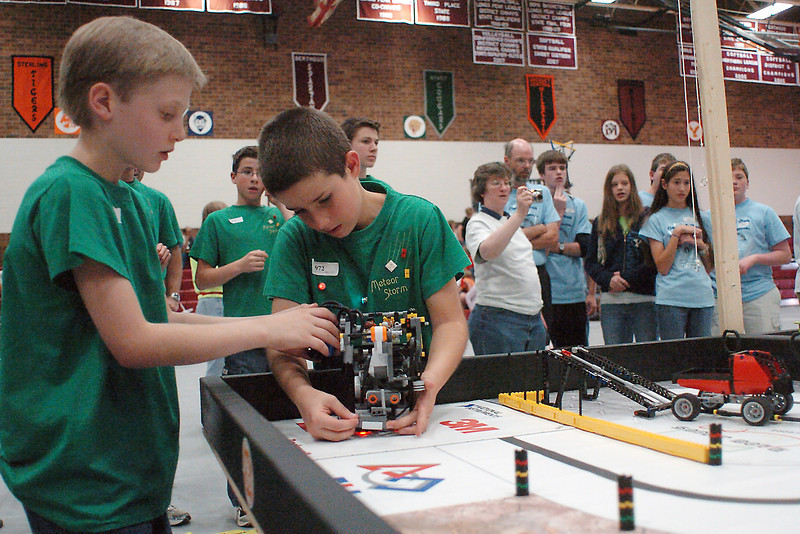 Daniel Warner, 9, left, and Joel Rozum, 9, of the Meteor Storm team from Loveland's Faith Evangelical Church make an adjustment to their robot during a demonstration run at the First Lego League Competition on Saturday at Berthoud High School.