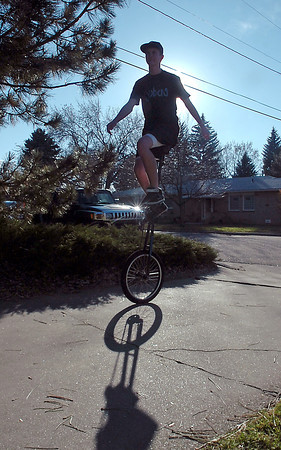Sean Tait rides on e of his many unicycles Wednesday in front of his Loveland home. He calls this unicycle the giraffe because it is so tall.