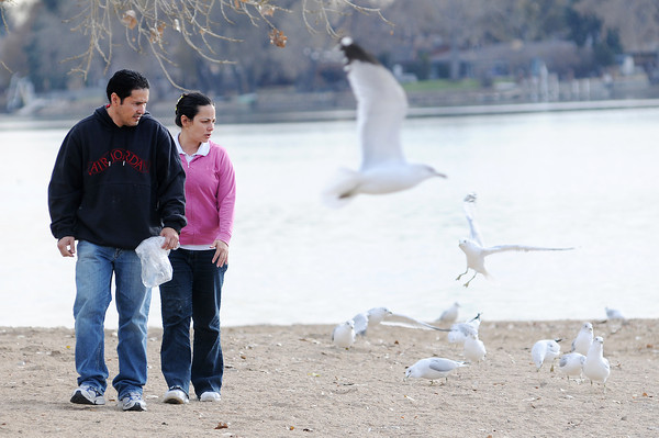 Loveland artist Alfredo Linares, left, and his wife Marielisa feed the birds on their daily walk at North Lake Park on Thursday. Today's weather is expected to be similar to yesterday's with partly cloudy skies and highs in the mid 70s.