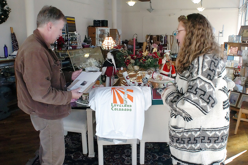 A Show of Hands owner Wendi Ward, right, chats with Scott Short as he drops off retro Loveland T-shirts he designed that will be offered for sale at Ward's new store located at 200 E. Fourth St. in downtown Loveland. The store's grand opening will be at 10 a.m. today.