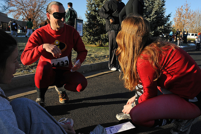 Tim Schmitt of Fort Collins, background, left, talks with his wife Patti, right, as they get ready for the Loveland Turkey Trot with Jennifer Rohde, also of Fort Collins on Thursday at McKee Medical Center.