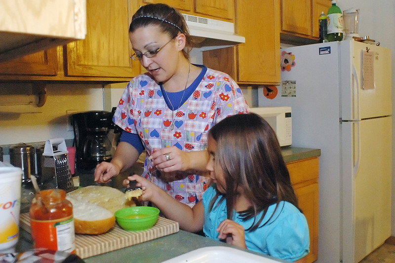 Amee Mjelde and her daughter, Sierra Cowher, 7, make garlic bread together while preparing dinner at their home in southwest Loveland on Tuesday, Nov. 24, 2009.