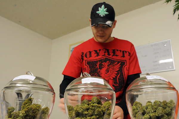 """Anthony Krepel, owner of Merry Janes Wellness Center, works the """"bud bar"""" during opening day of his medical marijuana dispensary on Thursday. His becomes the fifth such dispensary in Loveland."""