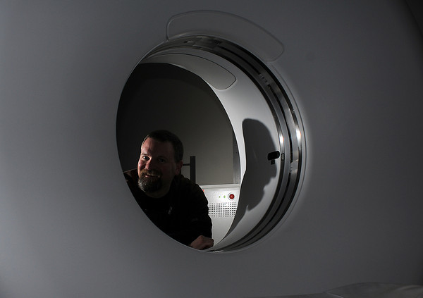 CT Technologist Jeremy Fritz of McKee Medical Center poses for a portrait through the opening of a new Adaptive Statistical Iterative Reconstruction scanner which reduces radiation dose by up to 40 percent across the entire body, without sacrificing image quality.