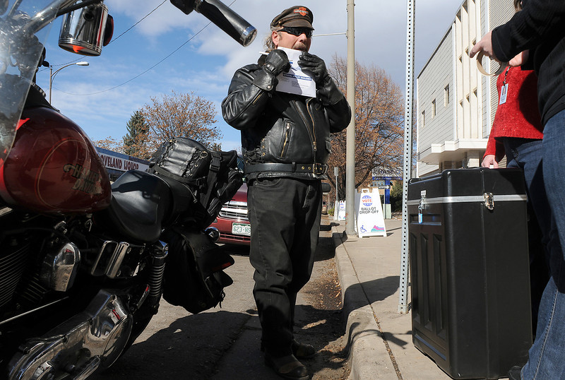Weston Pickett of Loveland seals his ballot before dropping it off at the Larimer County office at 205 East Sixth Street on Tuesday. Volunteers Megan Einerson, right, and Kimberly Hoefker said the drive-up drop-off was busy since earlier in the morning.