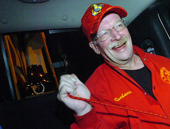 Loveland veteran Tom Buchanan laughs as he tugs on a rope to ring a bronze bell attached to the bed of a pick up truck while riding through the streets of Loveland before dawn on Veteran's Day.